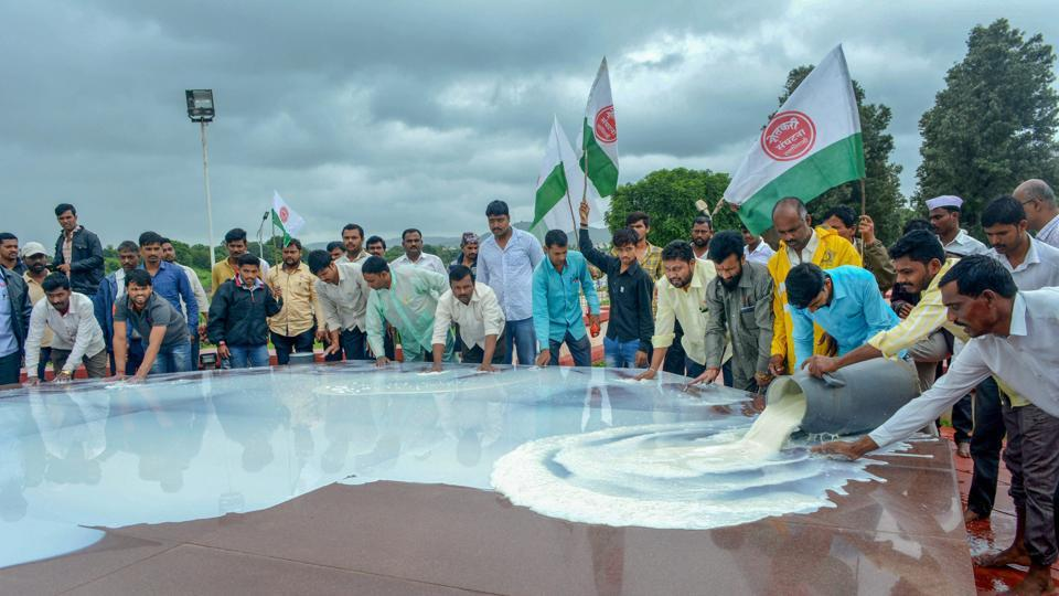 Swabhimani Shetkari Sanghatana activists pour milk at the memorial of Maharashtra's first Chief Minister late Y B Chavan during a protest to demand subsidy per liter and waiver of GST for butter and milk powder, in Karad on Monday.