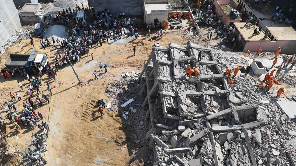 Fifteen hours after two buildings collapsed in Greater Noida's Shahberi village, National Disaster Response Force personnel and local police teams continued to dig through the rubble in search of labourers and a family of four on Wednesday. Three bodies had already been recovered by early that morning.  (Prakash Singh / AFP)