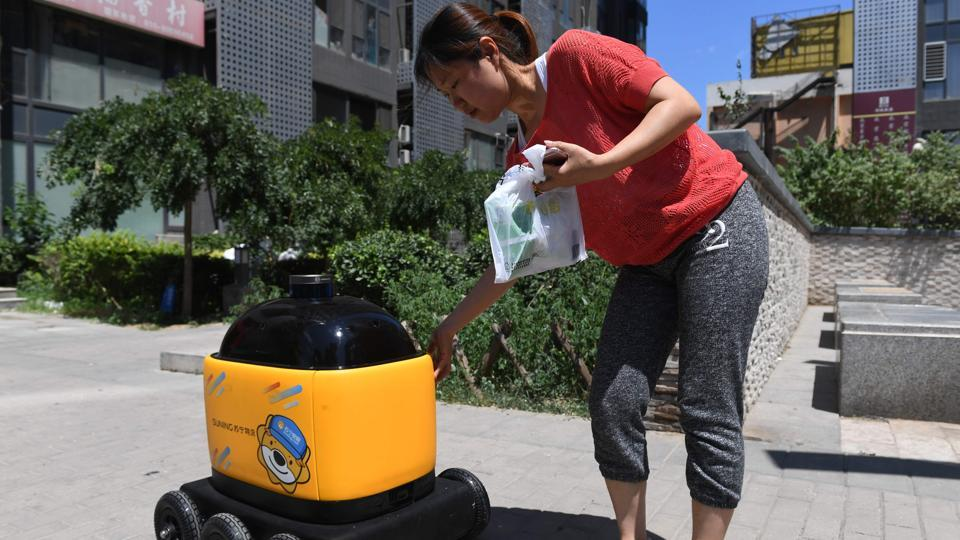 "A woman picks up groceries delivered by a Zhen Robotics delivery robot. Equipped with a GPS system, cameras and radar, the robots are seen by their creator as the future of logistics in China. To get a delivery via the ""little yellow horse"", the customer selects the desired products, taps in the address and pays via their phone. (Greg Baker / AFP)"