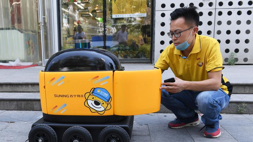 A worker loads a delivery robot with groceries. China is the world's biggest online shopping market with more than half of its population making at least one smartphone purchase per month, according to professional services firm PricewaterhouseCoopers. This compares to 14% in the rest of the world. (Greg Baker / AFP)