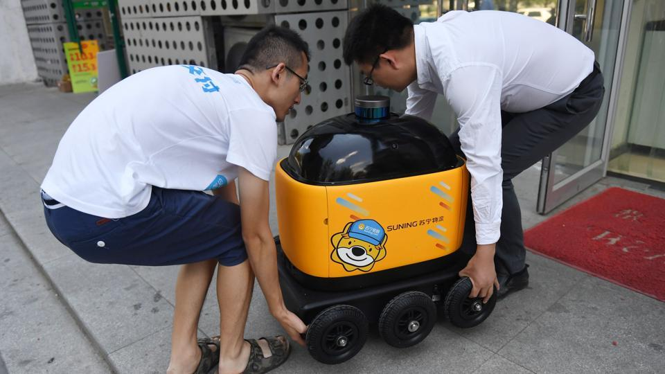 "Liu Zhiyong (R) founder and CEO of Zhen Robotics, and a colleague carry a delivery robot out of a Suning supermarket. ""At the moment, there are 100 million packages delivered every day in China. It will be one billion in the future,"" Liu said. ""There will not be enough humans to make the deliveries. We need more and more robots to fill this gap in manpower. And to reduce costs,"" added the CEO. (Greg Baker / AFP)"