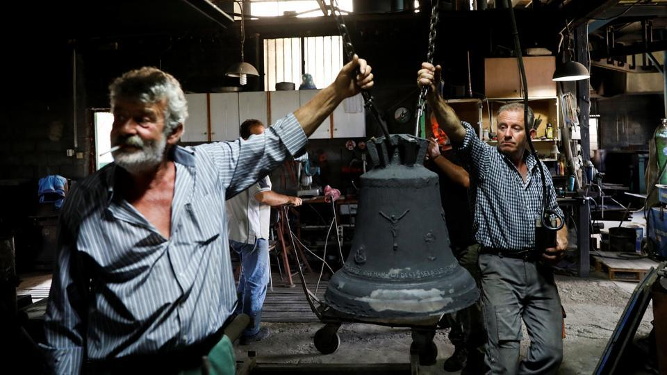 Thomas (L), 59, and Christos Galanopoulos, 55, prepare to clean a bell covered with sand. The Galanopoulos's biggest bell, weighing 3.5 tonnes, hangs from a church in northern Greece. But those days are gone. The volatile commodities market made the bells too costly to produce at times. Six people now work in the foundry, down from nine. (Alkis Konstantinidis / REUTERS)
