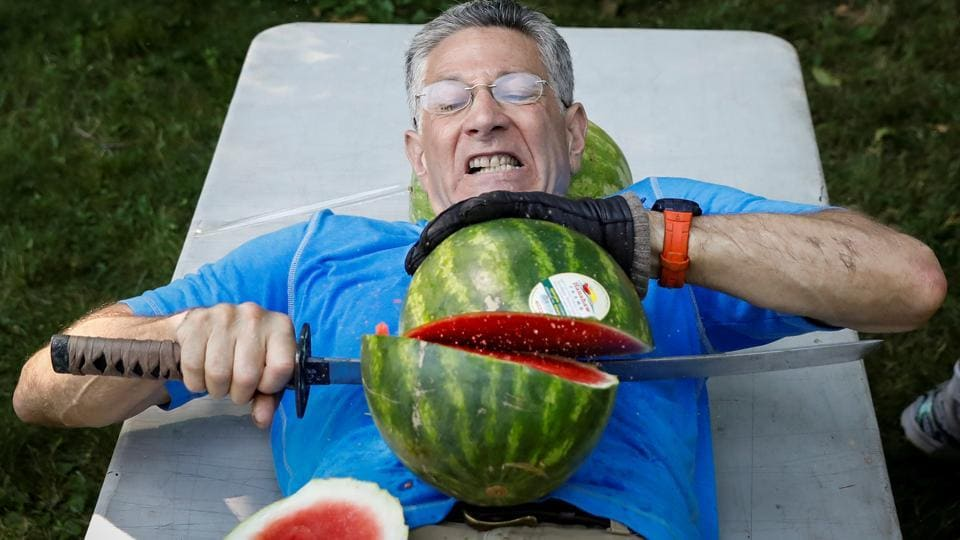 Ashrita Furman, who holds more Guinness World Records than anyone, attempts to set a new record for slicing the most watermelons in half on his own stomach in one minute in New York City. (Brendan McDermid / REUTERS)