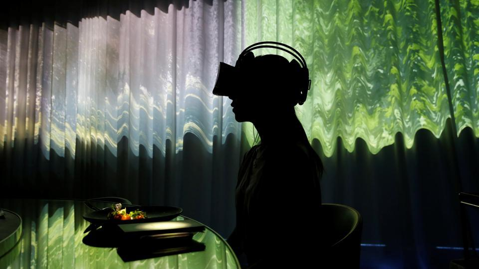 A woman wears VR glasses while projection mapping is cast on a table and walls during a media preview at