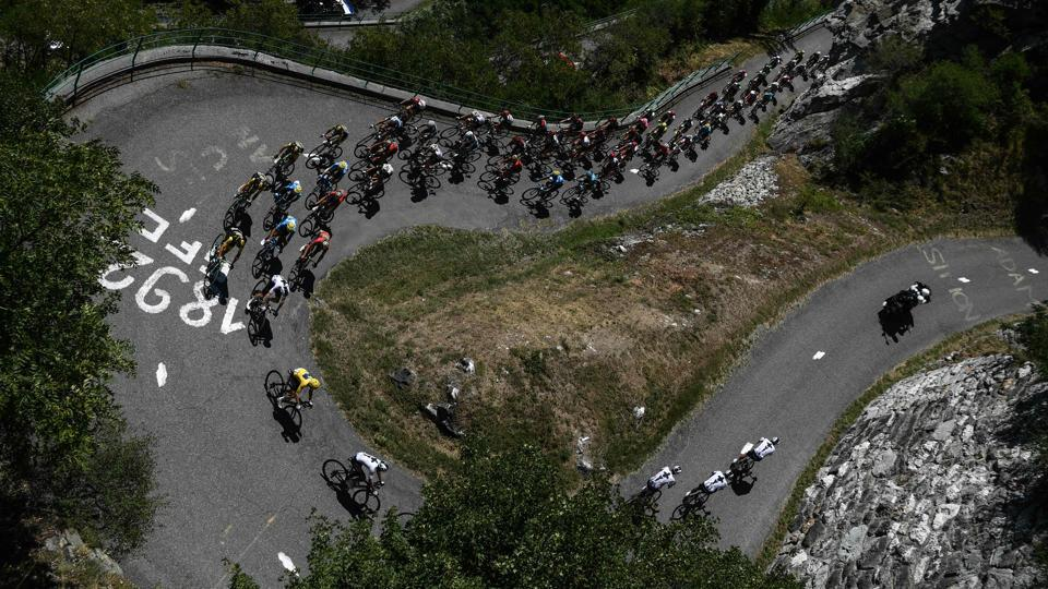The pack, with Great Britain's Geraint Thomas (front L), wearing the overall leader's yellow jersey, ascends the Montvernier bends during the twelfth stage between Bourg-Saint-Maurice - Les Arcs and l'Alpe d'Huez, on July 19, 2018. (Philippe LOPEZ / AFP)