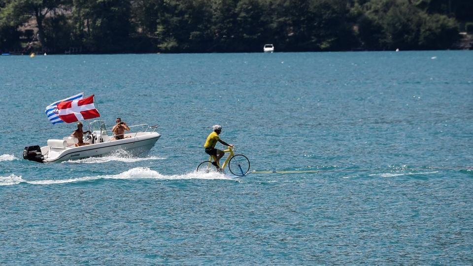 A man wearing a yellow jersey water skies on a bicycle on the Lake of Annecy during the tenth stage between Annecy and Le Grand-Bornand, French Alps, on July 17, 2018. (Jeff PACHOUD / AFP)