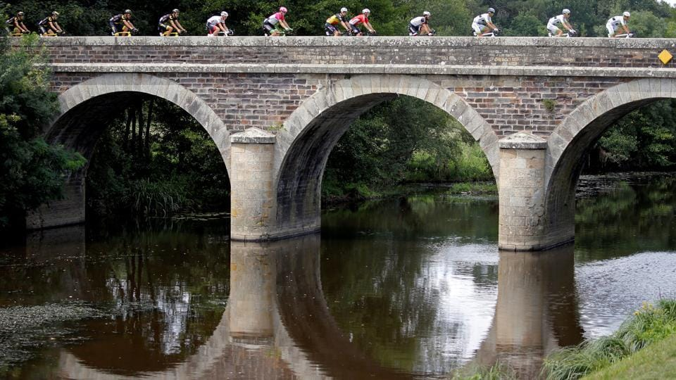 Cyclists race past a bridge during stage 4 from La Baule to Sarzeau on July 10, 2018. (Stephane Mahe / REUTERS)