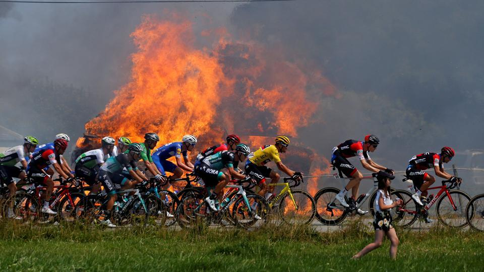 The peloton passes hay bales on fire during the stage 6 Brest to Mur-de-Bretagne Guerleden on July 12, 2018. (Stephane Mahe / REUTERS)
