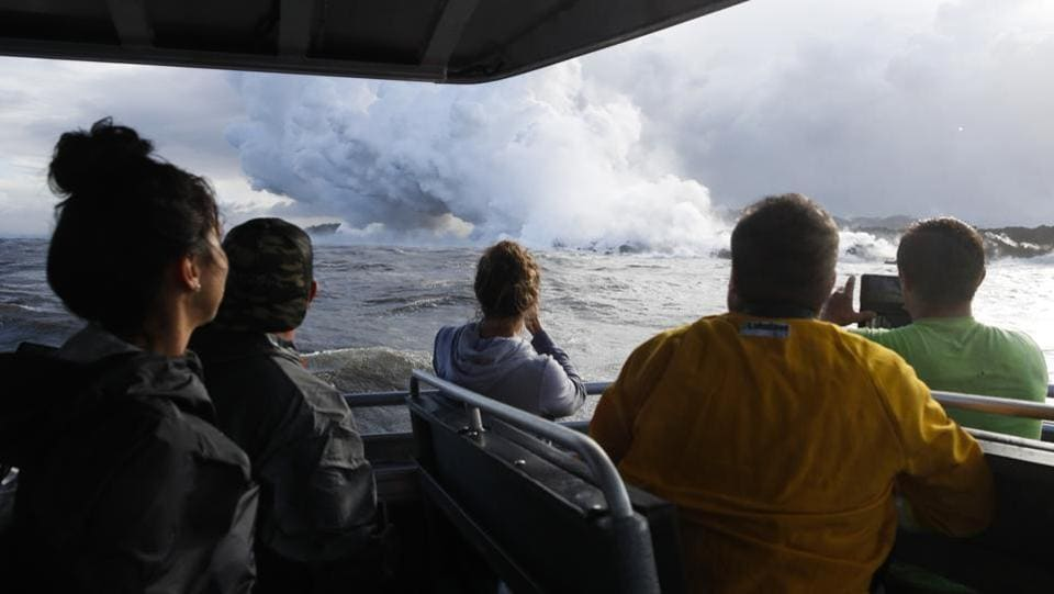 People watch a plume of steam as lava enters the ocean. One explosion sent lava flying through the roof of a tour boat off Big Island, injuring at least 13 people. Diane Ley, Hawaii County's director of research and development, said she's been working on setting up a lava viewing site for nearly two months. The injuries from the tour boat only validate the county's caution, she said. (Jae C. Hong / AP)
