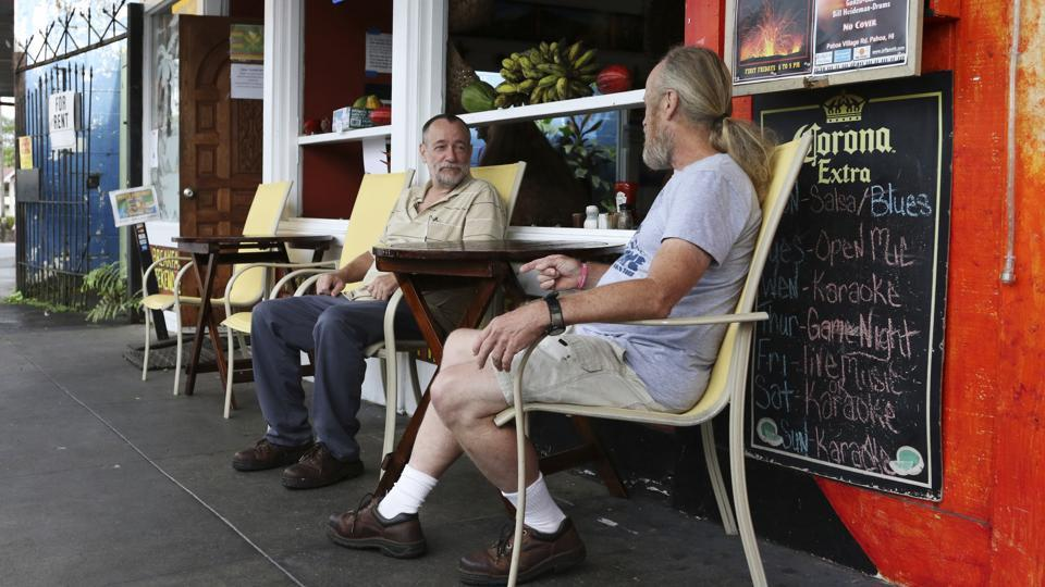 Brothers Ed (L), and Mike Arends, who evacuated their homes in the Leilani Estates area sit outside Pele's Kitchen restaurant in Pahoa. Restaurants and shops in Pahoa have lost 50 to 90% of their business, said Matthew Purvis, president of the Mainstreet Pahoa Association. This is partly because many residents have lost their homes and moved, but a significant chunk is because fewer tourists are visiting. (Caleb Jones / AP File)