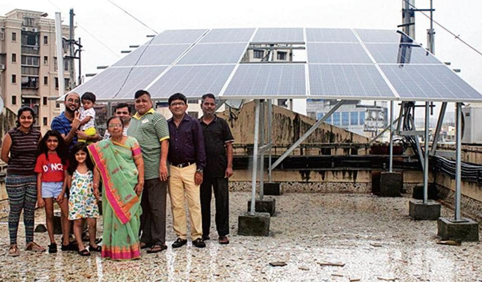 Residents of Arihant Darshan CHS stand beside their 11.05kWp rooftop solar plant.