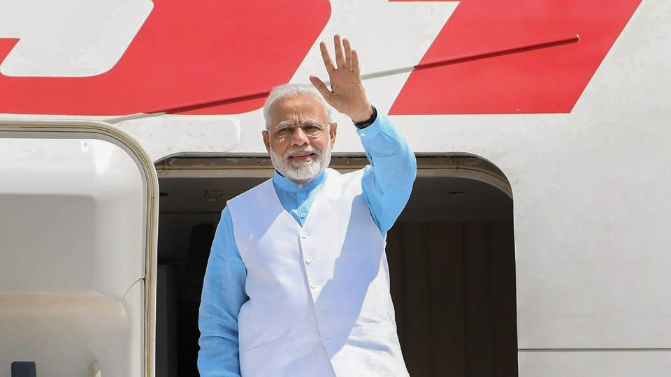 Prime Minister Narendra Modi waves as he emplanes for Rwanda, Uganda and South Africa from New Delhi, on Monday, July 23, 2018.