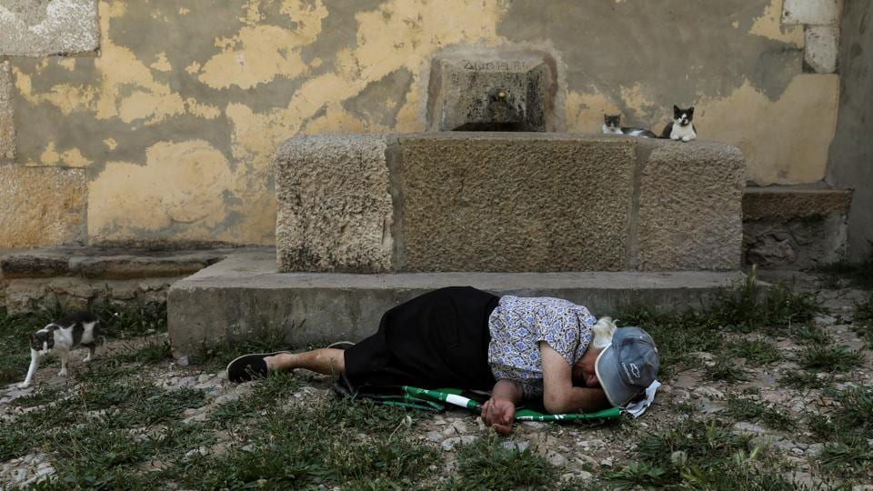 Sancho dozes off on the ground in the only square in the village. (Susana Vera / REUTERS)