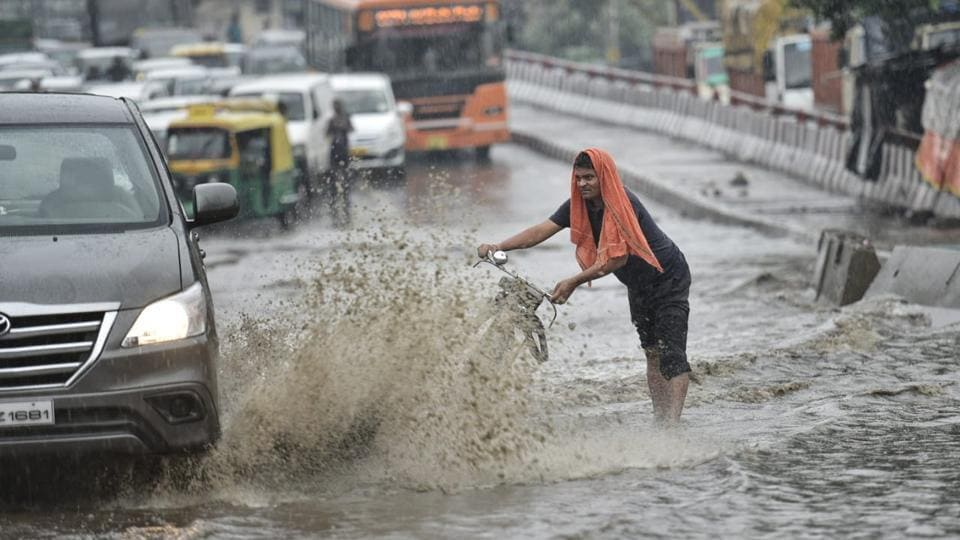 A man tries to save himself from a splash of water at Rohtak road near Anand Parbat. Residents of Delhi-NCR witnessed heavy rainfall on Thursday morning which led to waterlogging in several areas and brought rush-hour traffic to a virtual standstill. (Sanchit Khanna / HT Photo)