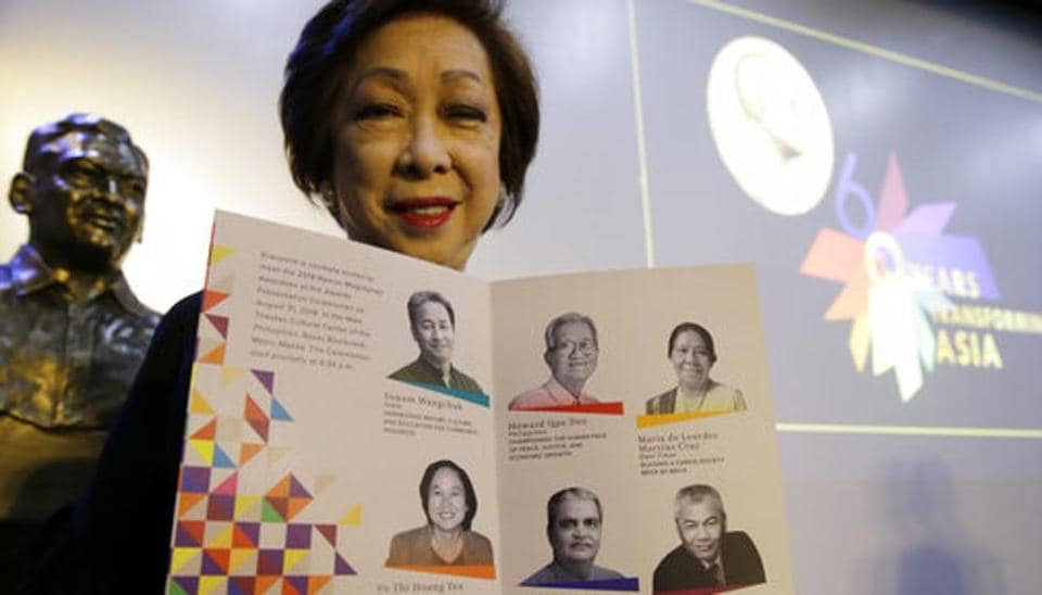 Ramon Magsaysay Award Foundation president Carmencita Abella poses with pictures of this year's awardees, regarded as an Asian version of the Nobel Peace Prize, in Manila, Philippines, Thursday.
