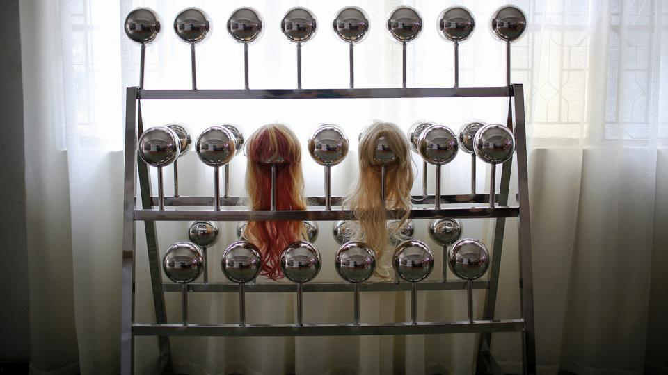 "Wigs are displayed on a shelf. ""Of course we're not expecting to make our AI dolls that human-like, after all we're just making adult products,"" said Liu Ding, WMDOLL product manager. ""But we will surely add more advanced technologies... for example making the limbs move more naturally,"" he added. (Aly Song / REUTERS)"