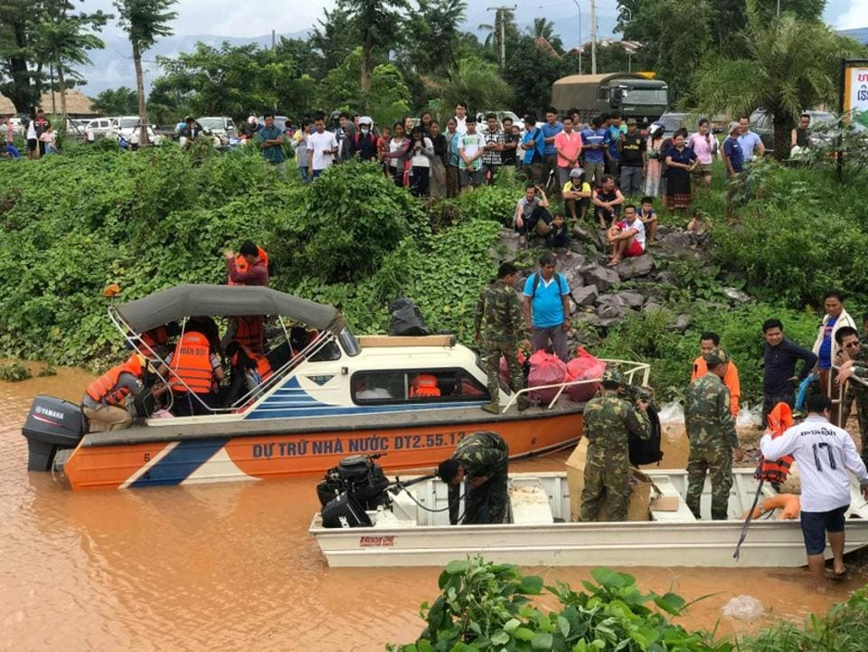 The search for survivors was hampered by monsoon weather. Boats and helicopters were dispatched to find people still trapped. Around a dozen Chinese rescuers in helmets and life jackets joined rescuers in Sanamxai town Thursday near the dam site. (Mime Phoumsavanh / REUTERS)