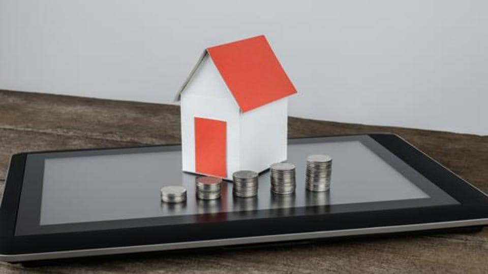 stacking coins and home model on tablet for saving with growing money to real estate owner in the future, Online marketing concept.