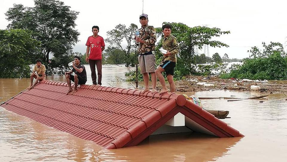 Residents climb up to rooftop surrounded by floodwaters in Attapeu province. Rescuers battled fresh rains Thursday to reach scores of people still missing after Xe-Namnoy dam  collapse in southern Laos that unleashed a torrent of water, washing away whole villages. (Attapeu Today / AFP)