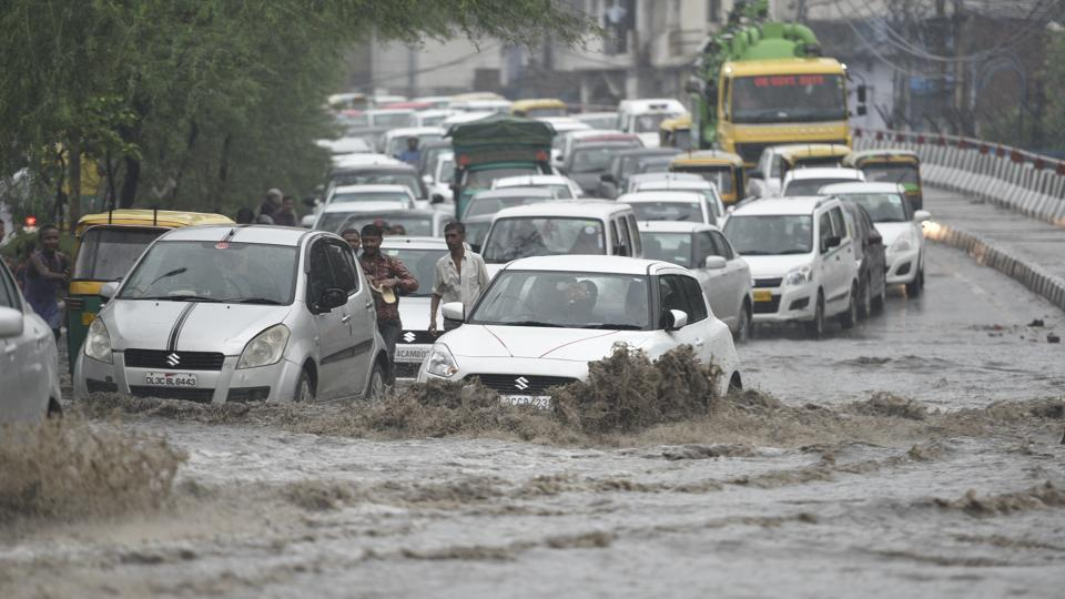 Traffic moves at a slow pace as vehicles cross a water logged street after heavy rains lashed the capital on Thursday.
