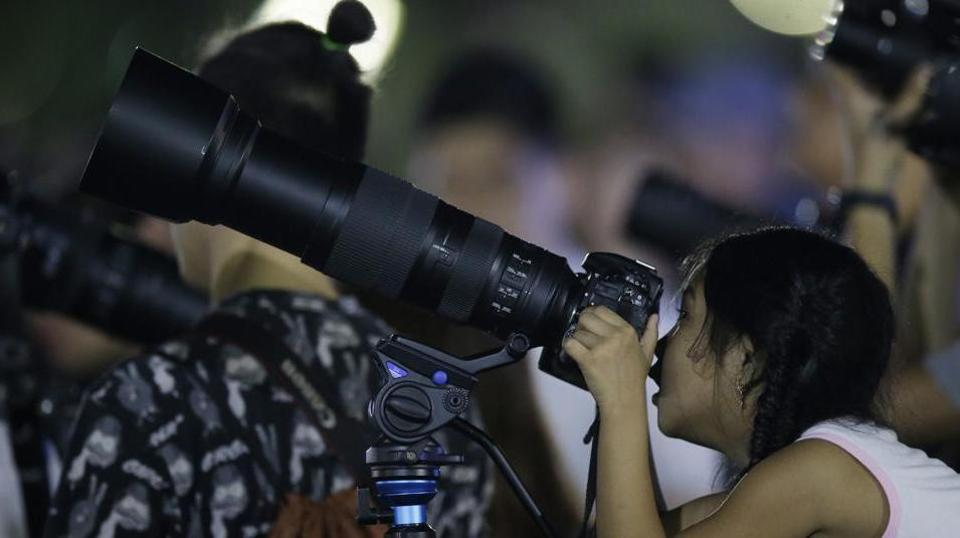 A girl peeks inside the viewfinder of a camera to see a lunar eclipse at a park in Manila, Philippines in January earlier this year.