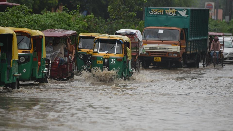 Commuters wade through a waterlogged street near Zakir Hussian College in New Delhi, on Friday.