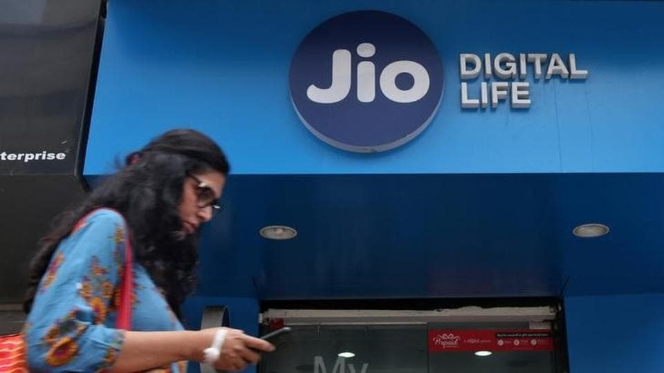 A woman checks her mobile phone as she walks past a mobile store of Reliance Industries' Jio telecoms unit.