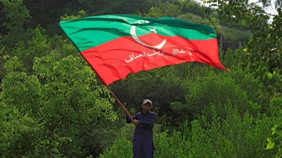 A supporter of cricket star-turned-politician Imran Khan, chairman of Pakistan Tehreek-e-Insaf (PTI), waves a party flag as he celebrates outside his residence in Islamabad, Pakistan, a day after polling in the general election.