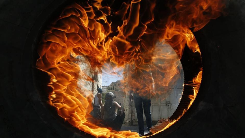 Palestinian protesters are seen through a burning tyre during clashes with the Israeli soldiers after the Friday prayers in the centre of the occupied West Bank city of Hebron on July 27, 2018. (Hazem Bader / AFP)