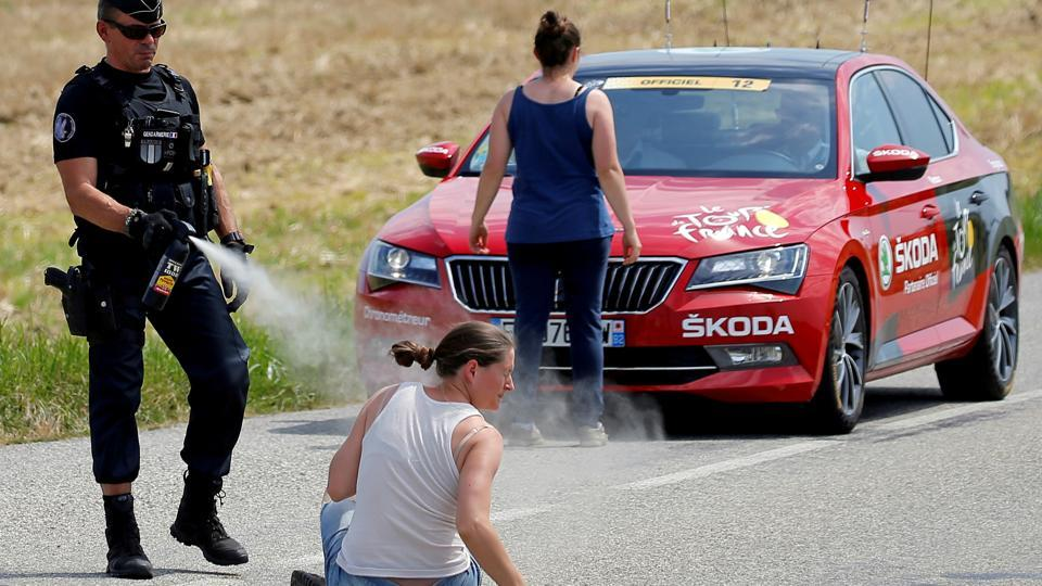 A police officer pepper sprays a protester as another protester stands in front of the race director's car during Stage 16 from Carcassonne to Bagneres-de-Luchon  of Tour de France on July 24, 2018. (Stephane Mahe / REUTERS)