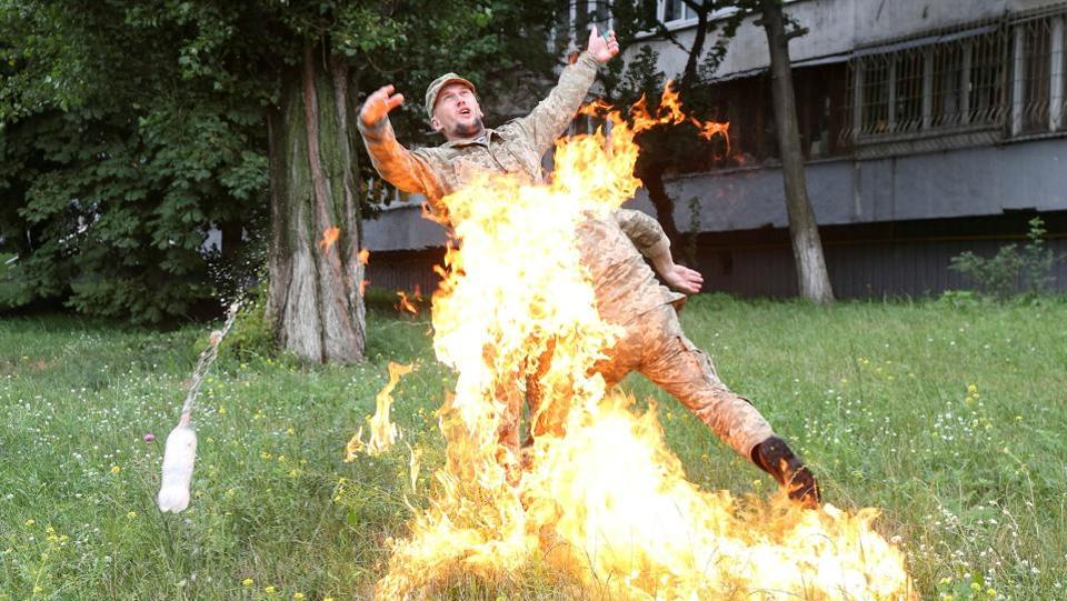 An officer on duty (R) attempts to knock down the flame as Ukrainian former serviceman Serhii Ulianov sets himself on fire while protesting against his dismissal from the Armed Forces in front of the Ukrainian Defence Ministry headquarters in Kiev, Ukraine on July 26, 2018. (Inna Sokolovska / REUTERS)