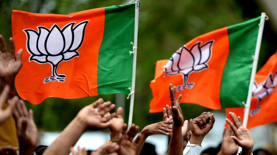 Supporters of Bhartiya Janta Party (BJP) wave party flags to their president Amit Shah on his arrival at Chennai on July 9, 2018.