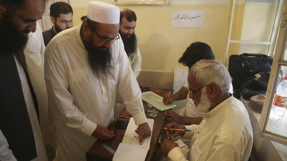 Hafiz Saeed, center, head of the Pakistani religious party Jamaat-ud-Dawa, affixes his thumb impression before casting a vote in Lahore, Pakistan, Wednesday, July 25, 2018.