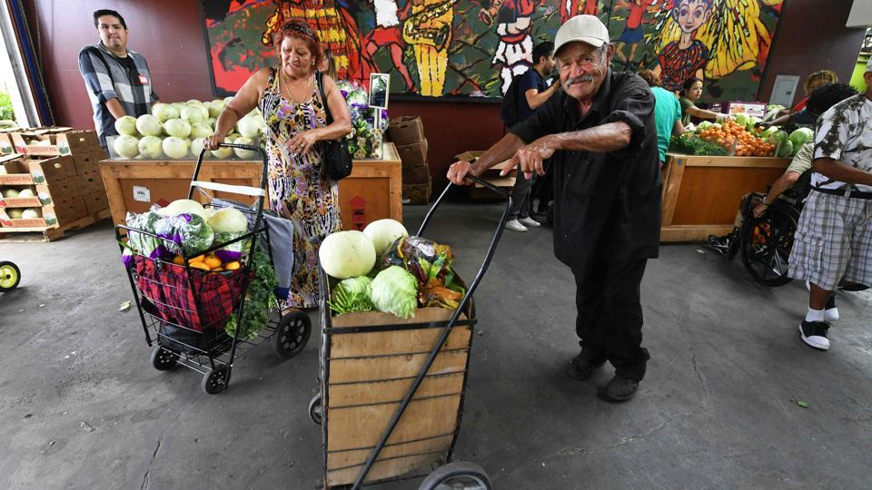 People pick their free fruit and vegetables on offer during a twice monthly food distribution effort in the Watts neighborhood of south Los Angeles, California. The NGO Food Forward is working to salvage food that Americans throw away every year and give it to the needy. The center also helps people find work, and offers assistance to young people applying to college. (Frederic J. Brown / AFP)