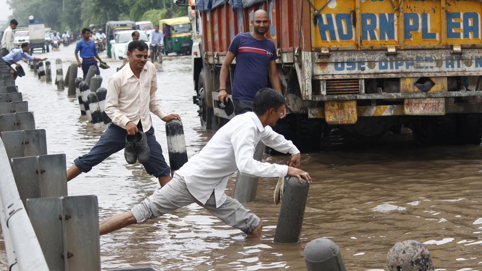 People try to make their way through a waterlogged road after heavy rains, at NH-48, near Sunbeam Company, in Gurugram. In Haryana, Rohtak, Sonipat, Narnaul, Panchkula, Ambala, Yamunanagar, Kurukshetra and parts of the NCR including Gurugram and Faridabad, recorded a fall in temperatures due to the rains. (Yogendra Kumar / HT Photo)