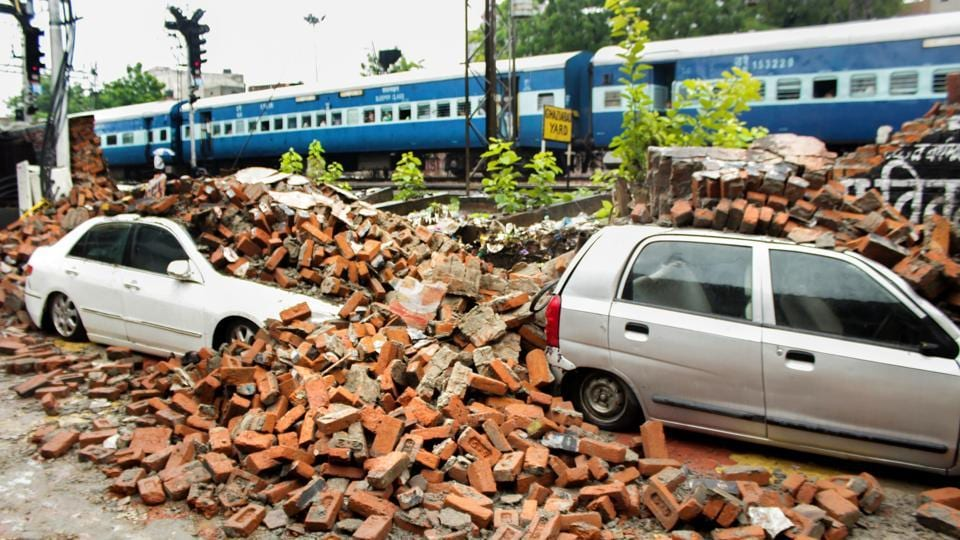 Damaged vehicles are seen after a boundary wall of Ghaziabad Railway Station collapsed due to monsoon rainfall, near Goushala Underpass in Ghaziabad. 116 families of Vartalok and Pragya Kunj housing societies were affected in Ghaziabad after a road caved in, on Thursday. (PTI)