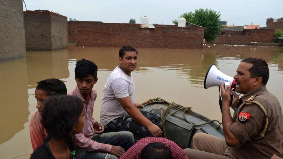 An officer makes announcement as he rescues the local residents who were struck during a flood-like situation after rainfall, at Mira Vihar Colony in Agra. Rains also damaged an outer boundary wall of the 16th century Fatehpur Sikri fort, west of Agra. However, there was no damage to the main monument, said an official, P.K. Singh. (PTI)