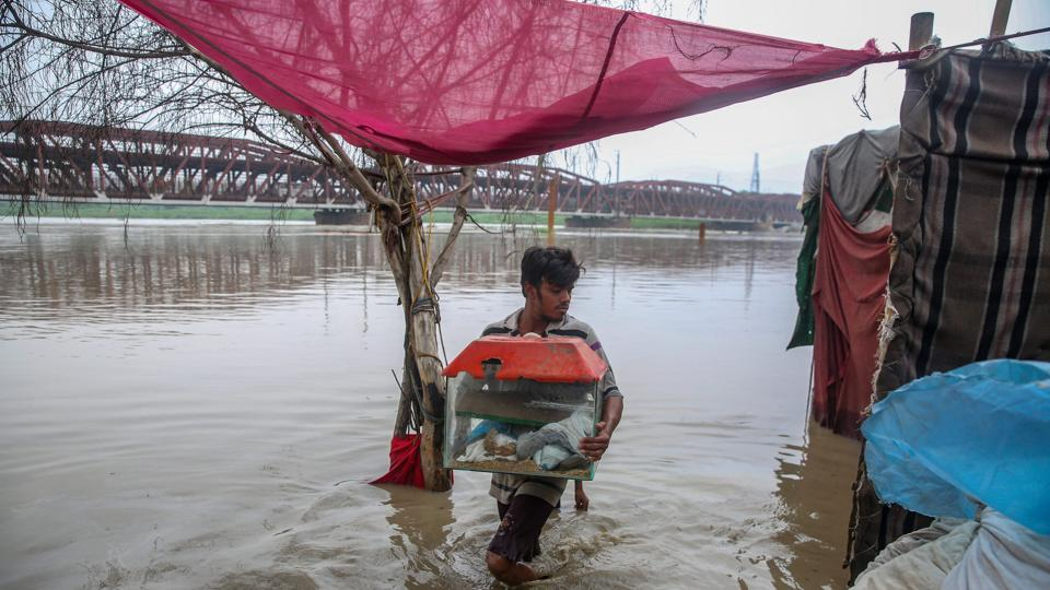 A boy their belongings to drier area as he evacuate the flooded Yamuna river bank in New Delhi on Saturday, July 28, 2018.