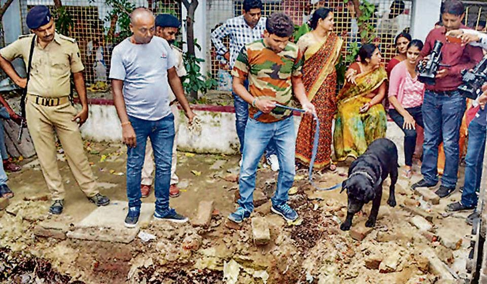 Muzaffarpur: Police with their sniffer dogs investigate the site where a rape victim was allegedly buried, at a government shelter home in Muzaffarpur, on Monday, July 23, 2018. A girl of the home has alleged that one of her fellow inmates was beaten to death and buried at the premises of the facility, and several were raped.