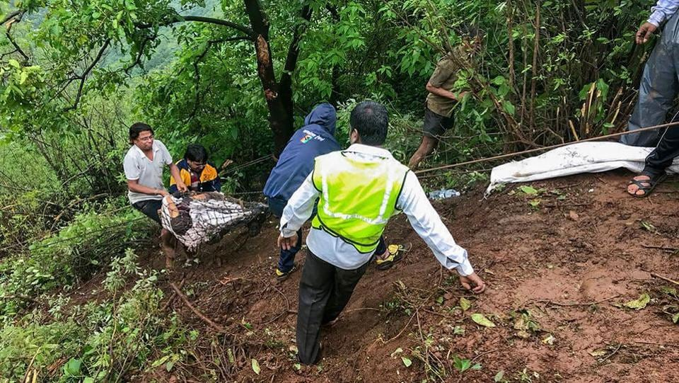 Mahabaleshwar trekker members take out bodies at the accident site where a bus carrying a group of staff members of an agriculture university, fell into a 500-ft gorge in the Konkan region, killing 33 passengers, in Raigad on Saturday. (PTI)