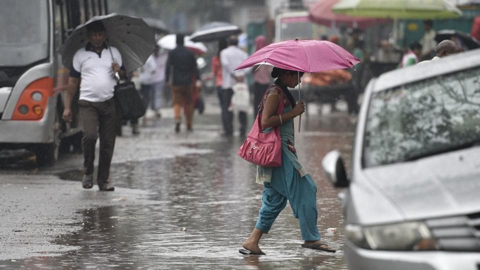 Commuters holding umbrellas as they walk during rain in New Delhi on July 27.