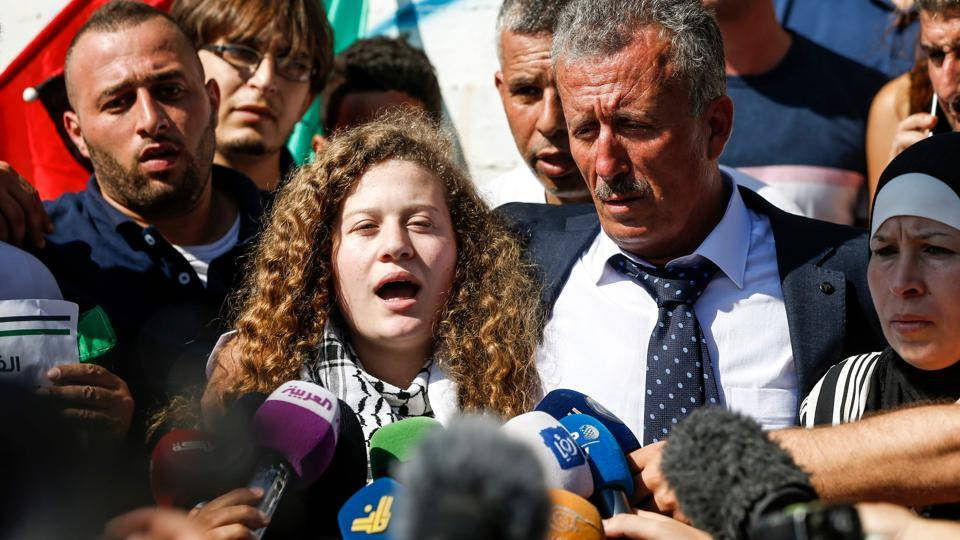 Palestinian activist and campaigner Ahed Tamimi speaks to reporters upon her release from prison after an eight-month sentence for slapping two Israeli soldiers, on the outskirts of the West Bank village of Nabi Saleh on July 29, 2018, as she is accompanied by her father and mother.