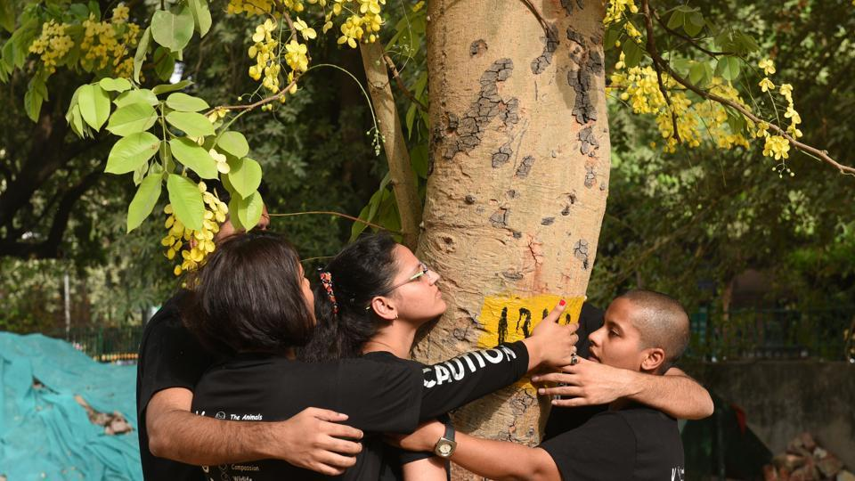 People hug a tree to protest against a redevelopment plan inSarojini Nagar in Delhi on June 24, 2018.