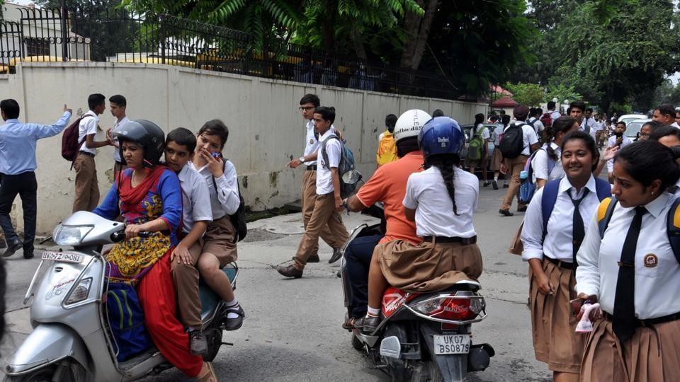 Parents carry their children from school in Dehradun on Monday.