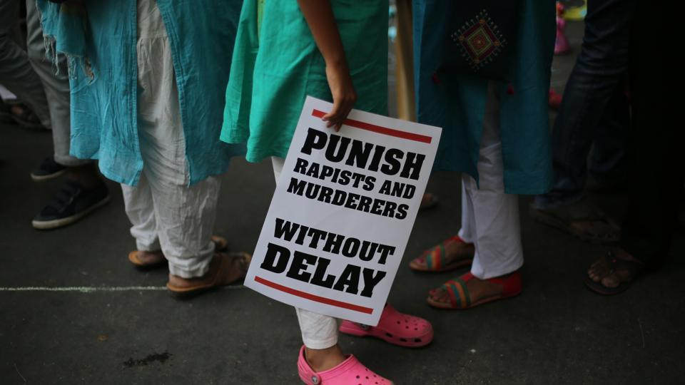 A protestor stands with a placard during a protest in New Delhi, India.
