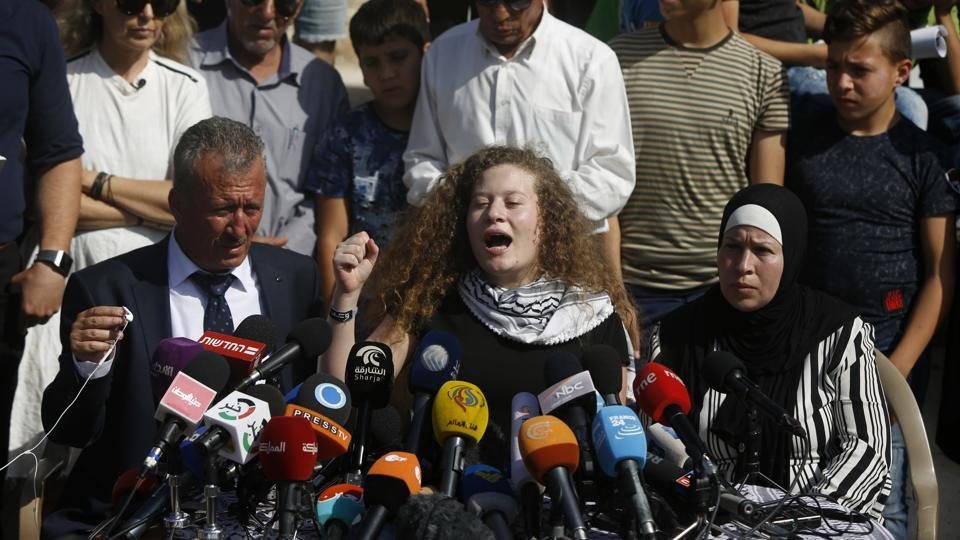 Ahed Tamimi speaks sitting between her father Bassam and mother Nariman during a press conference on the outskirts of the West Bank village of Nabi Saleh near the West Bank city of Ramallah, Sunday, July 29, 2018.