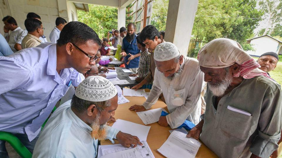 People check their names on the final draft of the state's National Register of Citizens after it was released, at a NRC Seva Kendra in Nagaon, July 30