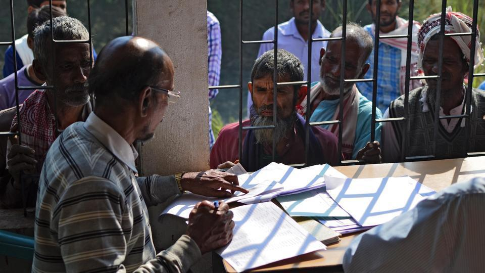 People wait to check their names on the first draft of the National Register of Citizens at Goroimari of Kamrup district in Assam.