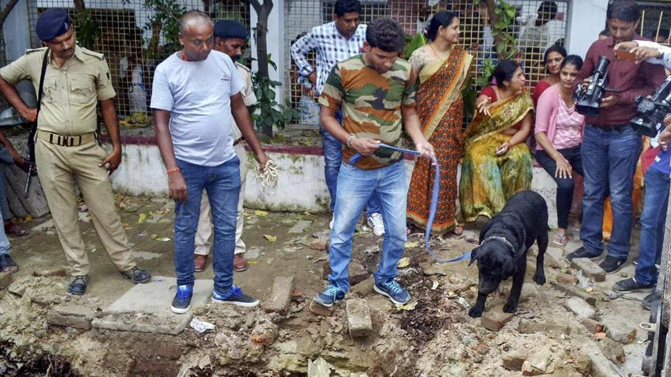 Police with their sniffer dogs investigate the site where a rape victim was allegedly buried, at a government shelter home in Muzaffarpur, on Monday, July 23, 2018.