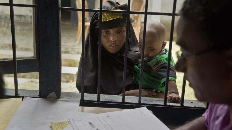 A woman holding her child checks if their names are included in the National Register of Citizens at a draft center. The Assam government started the process of updating the NRC in December 2013. All residents in the state were asked to produce documents proving that they or their families had lived in India before March 24, 1971. (Anupam Nath / AP)